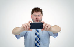 Businessman photographed by smartphone, surprise Stock Images
