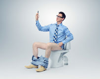 Businessman photographing himself in the toilet Royalty Free Stock Image