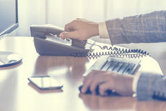 Businessman pick up or hangs up the voip phone. Businessman use the phone in the office, keyboard, mouse, mobile, and monitor detail in the background Royalty Free Stock Photos