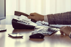 Businessman pick up or hangs up the voip phone. Businessman use the phone in the office, keyboard, mouse, mobile, and monitor detail in the background stock images