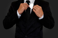 Businessman picking pasteboard. Businessman in black suit picking pasteboard out of pocket on gray background Royalty Free Stock Photography