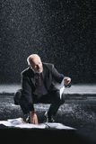 Businessman Picking Soaked Documents In Rain Royalty Free Stock Photography