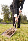 Businessman picking up droppings with a shovel Stock Photo