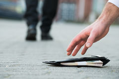 Businessman Picking Up Fallen Wallet With Money royalty free stock image
