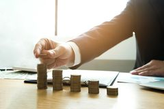 Businessman picks coins on the table, counts money . Business co stock photos
