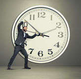 Businessman picks up the clock Royalty Free Stock Images