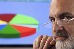 Businessman and Pie Chart. Close-up portrait of a businessman looking pensively at the camera. A computer monitor displaying a multi-colored pie chart can be Stock Photo
