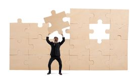 Businessman with a piece of puzzle. Build the business concept royalty free stock photo