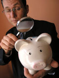 Businessman with a piggy bank. Businessman looks to piggy bank through a magnifying glass (focus on piggy bank stock photos