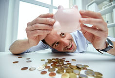 Businessman with piggy bank and coins at office Royalty Free Stock Photos