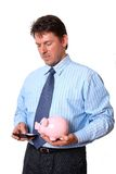 Businessman with piggy bank in hand calculate on t Stock Photos