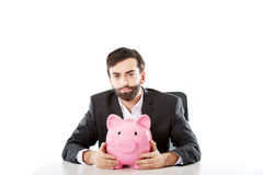 Businessman with piggybank by a desk. Stock Photos