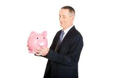 Businessman with piggybank. Smiling mature businessman with piggybank Stock Image