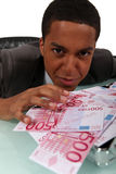 Businessman with a pile of cash Stock Photo