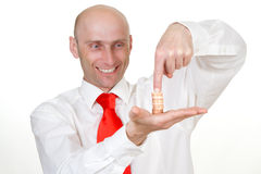 Businessman with pile of coins. Smiling young businessman with finger pressing stack of coins in palm of hand, isolated on white background royalty free stock photo