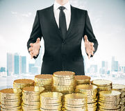 Businessman with pile og gold coins at city backgroound Royalty Free Stock Images