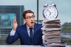 Businessman with pile stack of paper paperwork and an alarm cloc Stock Image