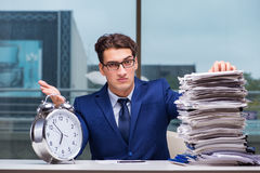 Businessman with pile stack of paper paperwork and an alarm cloc Stock Photos