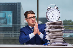 Businessman with pile stack of paper paperwork and an alarm cloc Stock Images