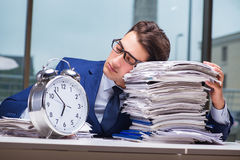 Businessman with pile stack of paper paperwork and an alarm cloc Royalty Free Stock Image