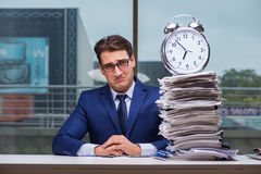 Businessman with pile stack of paper paperwork and an alarm cloc. K working in the office Stock Image
