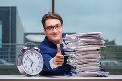 Businessman with pile stack of paper paperwork and an alarm cloc. K working in the office Royalty Free Stock Photos