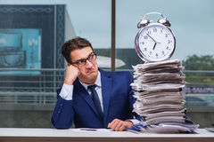 Businessman with pile stack of paper paperwork and an alarm cloc. K working in the office Royalty Free Stock Photo