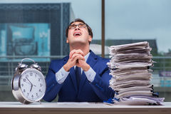 Businessman with pile stack of paper paperwork and an alarm cloc. K working in the office Royalty Free Stock Image
