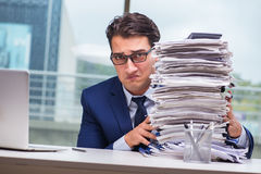 The businessman with pile stack of paper paperwork in the office. Businessman with pile stack of paper paperwork in the office Stock Photo