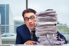 The businessman with pile stack of paper paperwork in the office. Businessman with pile stack of paper paperwork in the office Royalty Free Stock Photography