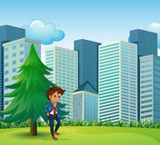 A businessman beside the pine tree near the tall buildings Royalty Free Stock Images