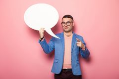 Handsome man in bright jacket with speech bubble. Businessman in pink jumper, blue jacket and glasses holds blank paper thinking speech bubble with empty space Royalty Free Stock Photos