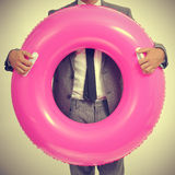 Businessman with a pink swim ring, with a retro effect. A young caucasian businessman wearing a grey suit with a pink swim ring, with a retro effect Royalty Free Stock Photography