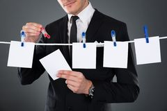 Businessman pinning blank papers on clothesline Stock Photo