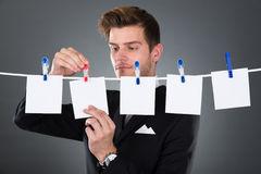 Businessman Pinning Blank Papers On Clothesline Royalty Free Stock Images