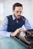 Businessman with pipe in his mouth working on typewriter Royalty Free Stock Images