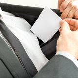 Businessman placing a blank business card in the inner pocket of Stock Photography