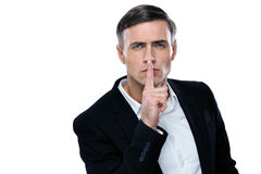 Businessman placing finger on lips saying shhh. Be quiet royalty free stock image