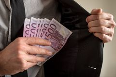 Businessman placing six five hundred Euro bills in the inner pocket of his suit jacket. Conceptual of bribery royalty free stock image