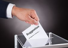 Businessman placing suggestion slip into box. Cropped image of businessman placing suggestion slip into box over black background royalty free stock images