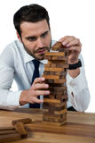 Businessman placing wooden block on a tower Royalty Free Stock Photos