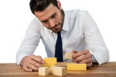 Businessman placing wooden block on a tower Stock Photos