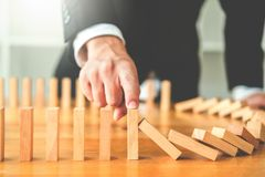Businessman plan and strategy in business Domino Effect Leadership Management Solution concept.  stock photos