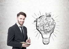 Businessman with a planner, a lightbulb scheme Royalty Free Stock Photos