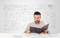 Businessman planning and calculating with various business ideas. Young businessman planning and calculating with various business ideas Stock Images