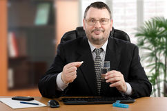 Businessman plans to take a pill at lunchtime. Businessman in black suit holds white pill by right hand and glass water with left hand. He is ready to take a Stock Photography