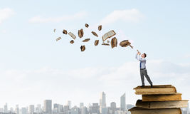 Businessman play pipe. Young carefree businessman on pile of old books playing pipe Royalty Free Stock Image