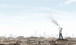 Businessman play pipe. Young carefree businessman on pile of old books playing pipe Stock Photography