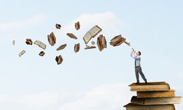Businessman play pipe. Young carefree businessman on pile of old books playing pipe Royalty Free Stock Photo