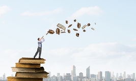 Businessman play pipe. Young carefree businessman on pile of old books playing pipe Royalty Free Stock Photos